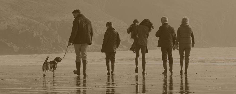 family walking dog on beach